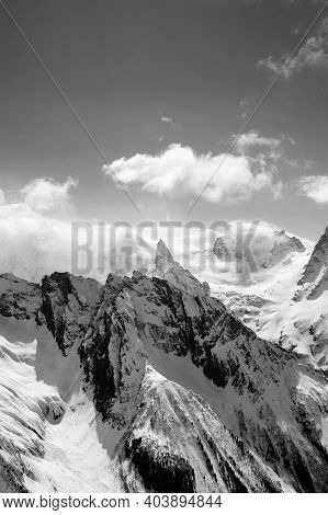 Black And White View On Snowy High Mountains Peak In Sunlit Clouds At Winter Evening. Caucasus Mount