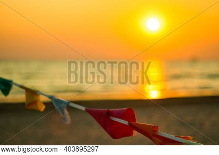 Closed Beach. Colorful Multicolored Flags On The Background Of The Sea Sunset. Water Background, Wat