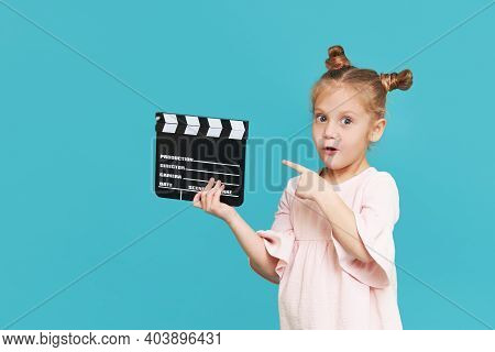 Funny Smiling Child Girl Hold Film Making Clapperboard Isolated On Blue Background. Little Clipmaker