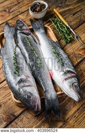 Raw Seabass Fish On A Tray. Wooden Background. Top View