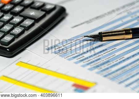 Calculator And Pen With Accounting Report And Financial Statement On Desk. Accounting Business Plan