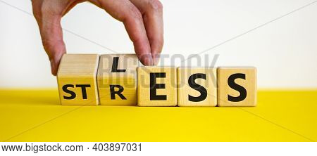 Having Less Stress Or Being Stress-less. The Word 'stress' And 'less' On Wooden Cubes. Male Hand. Be
