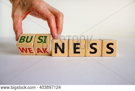 Business Or Weakness Symbol. Businessman Hand Turns Wooden Cubes And Changes The Word 'weakness' To