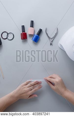 Female Hands File Nails On Light Gray Background. Nearby Are Laid Out Accessories For Manicure Nail