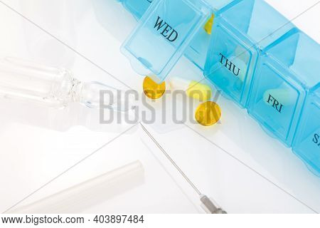 Tablet Organizer With Various Tablets, Syringe And Injection Ampoule. Weekly Pill Organizer Isolated