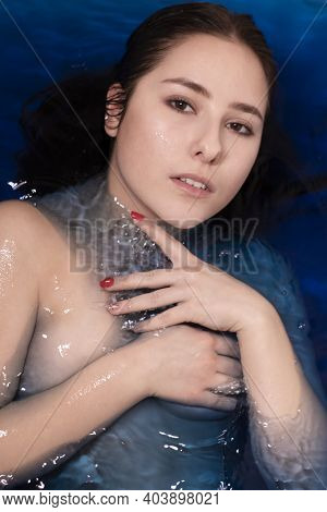 Portrait Of Attractive Brunette Woman Topless In Blue Liquid. In Bathtub With Colored Water. Drownin