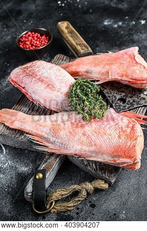 Whole Raw Red Snapper Fish On A Cutting Board. Black Background. Top View