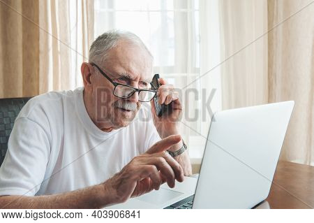 Male Senior Gray Hair Working Laptop Interior. A Gray-haired Man Of 87 Years Old Speaks On The Phone