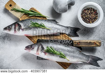 Raw Fresh Fish Seabass And Ingredients For Cooking. White Background. Top View