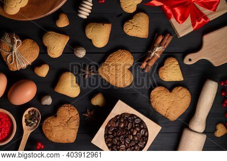 Gingerbread Heart Shaped Cookies, Spices, Coffee Beans And Baking Supplies, On Black Wood Background