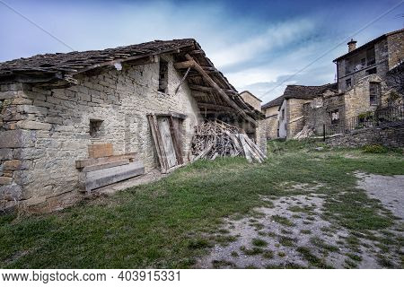 Typical Old Farm Of The Pyrenees, Borda, With A Pile Of Wood Stacked On The Door, Rural Landscape, V