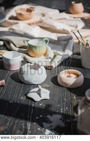 A Close-up View Of Clay Plates And A Paint Brush On A Wooden Table And Dried Flowers On A Background