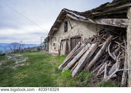 View Of An Old Farm Typical Of The Pyrenees, Borda, With A Pile Of Wood Stacked On The Door, Rural L