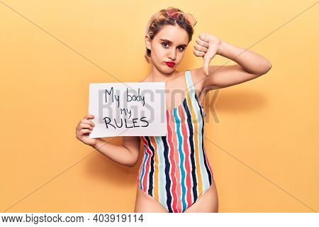 Young beautiful blonde woman wearing swimwear holding my body my rules banner with angry face, negative sign showing dislike with thumbs down, rejection concept