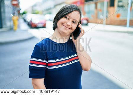 Beautiful brunette woman with down syndrome at the town on a sunny day talking on smartphone