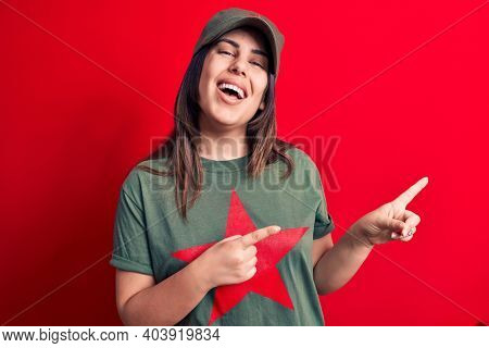 Young beautiful brunette woman wearing cap and t-shirt with red star communist symbol smiling and looking at the camera pointing with two hands and fingers to the side.