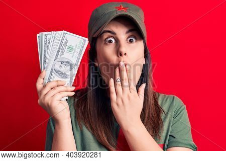 Woman wearing t-shirt with red star communist symbol holding bunch of dollars banknotes covering mouth with hand, shocked and afraid for mistake. Surprised expression