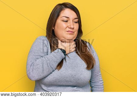 Beautiful brunette plus size woman wearing casual clothes touching painful neck, sore throat for flu, clod and infection