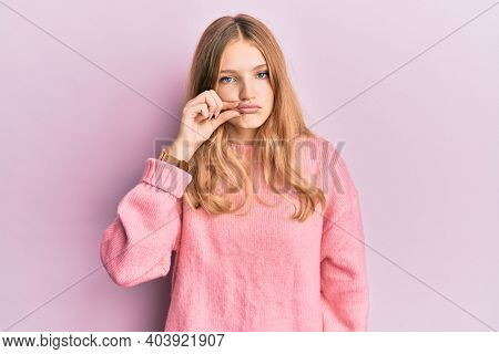 Beautiful young caucasian girl wearing casual clothes mouth and lips shut as zip with fingers. secret and silent, taboo talking