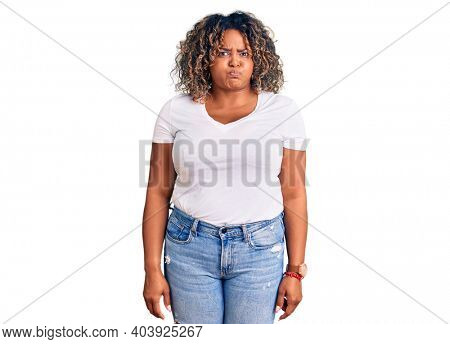 Young african american plus size woman wearing casual clothes puffing cheeks with funny face. mouth inflated with air, crazy expression.