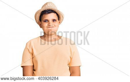 Little boy kid wearing summer hat and hawaiian swimsuit puffing cheeks with funny face. mouth inflated with air, crazy expression.