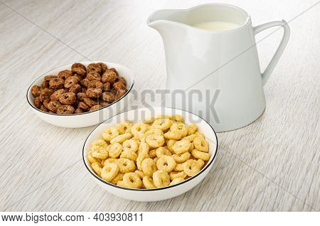 Toasted Cereal Breakfasts With Chocolate And Caramel In White Bowls, Pitcher With Yogurt On Wooden T