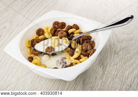 Spoon In White Bowl With Toasted Cereal Breakfasts And Yogurt On Wooden Table