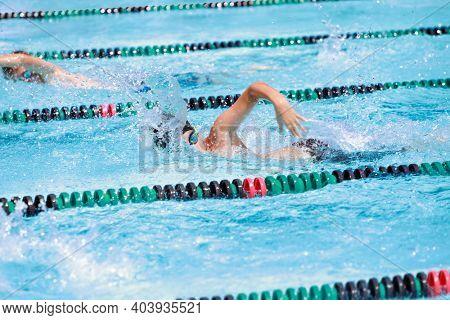 Motion blurred swimmer in a freestyle race, focus on shoulder and water drops