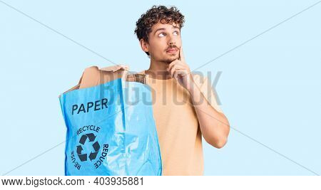 Young handsome man with curly hair holding recycling wastebasket with paper and cardboard serious face thinking about question with hand on chin, thoughtful about confusing idea