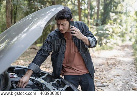Man Use A Cellphone Call Garage In Front Of The Open Hood Of A Broken Car On The Road In The Forest.