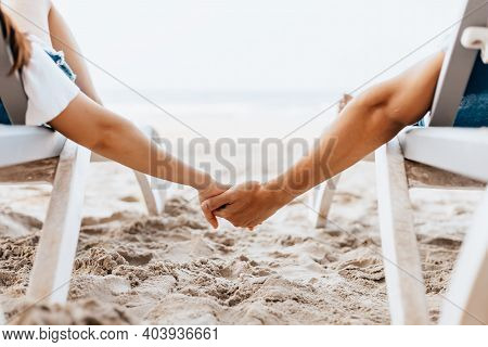 Couple Of Lovers Sitting On Beach Chair Holding Hands On The Beach In The Morning.  Newlywed Couple