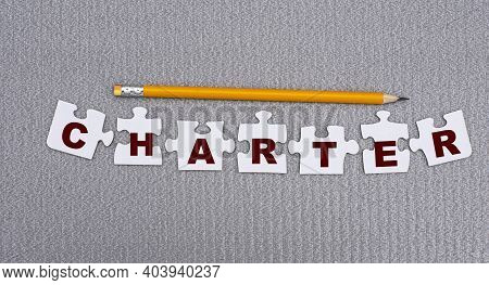 Charter Is A Word Made Up Of Paper White Puzzles On A Gray Background And In Pencil. Info Concept