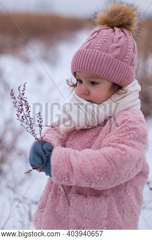 A Little Girl In A Pink Fur Coat Is Having Fun, Playing Outside, Surrounded By Snow. Winter Time, Th