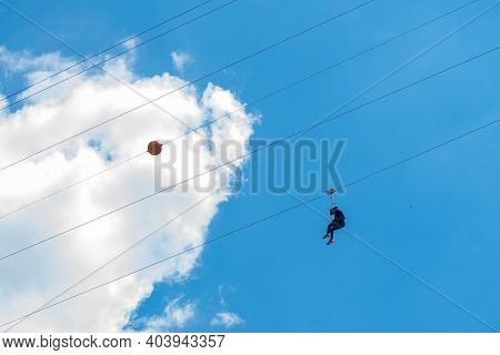 Bukovel, Ukraine - May 27, 2018: Chairlift And Man On Blue Sky Background.
