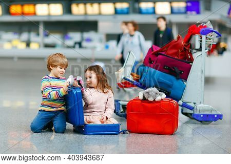 Cute Little Girl And Boy At Airport. Tired Children, Siblings Sitting On Ground And Waiting For Dela