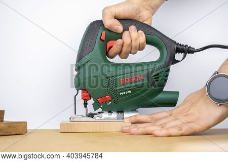 Modern Electric Jig Saw Tool In A Hand For Diy Home Woodworking. Wood Boards On Background