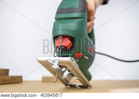 Modern Electric Jig Saw Tool With Jigsaw File Close Up For Diy Home Woodworking. Wood Boards On Back