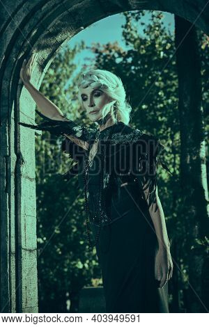 Black Widow. An aristocratic old widow woman with beautiful gray hair and a rich black dress stands sad in the arch of the castle. Fantasy World. Halloween.