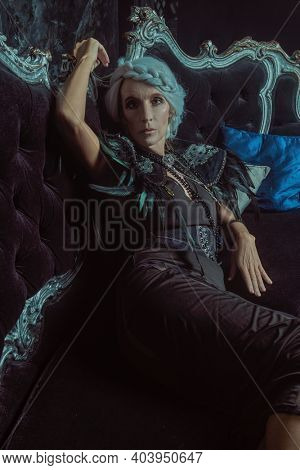 Black widow. A beautiful old woman, a noble widow with gray hair and a rich black dress, sits on a vintage sofa in her old castle. Fantasy world. Halloween.