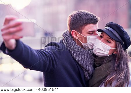 Happy couple celebrating Valentines Day in masks during covid-19 pandemic