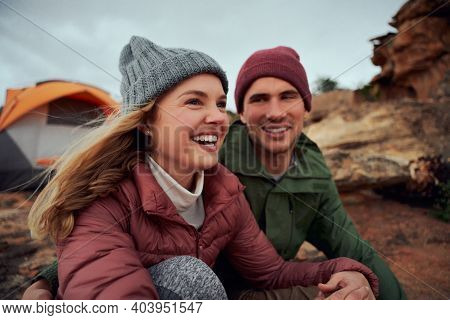 Happy Young Couple Relaxing During Camping Sitting Outside Tent Looking Away During Winter