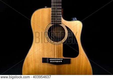 Body Of A Classic Acoustic Six-string Guitar With A Yellow Sound Board And Black Pickguard On Isolat