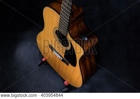 Top View On Body Of Classic Yellow Acoustic Guitar With Steel Strings On Black Isolated Background