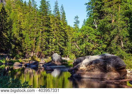 The shady forest is reflected in the water. Charming little lake in the Yosemite Valley. Yosemite Park is located on the slopes of the Sierra Nevada