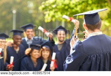 education, graduation, technology and people concept - group of happy international graduate students in mortar boards and bachelor gowns with diplomas taking picture with smartphone outdoors