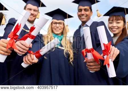 education, graduation and people concept - group of happy international graduate students in mortar boards and bachelor gowns with diplomas