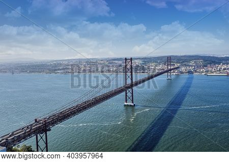 The 25 De Abril Bridge Over The Tagus River Is A Bridge Connecting The City Of Lisbon To The Municip