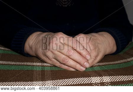 Senior Woman's Folded Hands Lie On A Plaid Blanket. Wrinkles On The Hands. Loneliness Of The Elderly