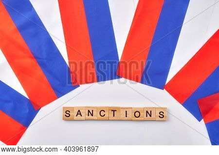 Sanctions Against Russia Concept. Russian Flags And Wooden Cubes.