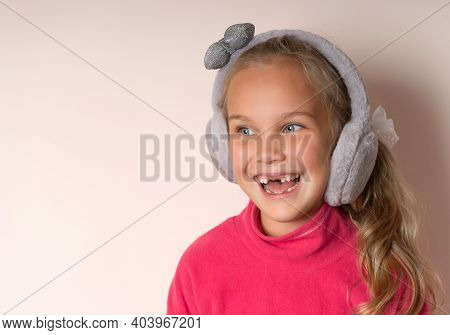Little Cute Toothless Girl Smiling In Warm Fur Headphones On A Light Background